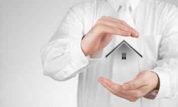 Property insurance and security concept. Protecting gesture of woman and symbol of house.